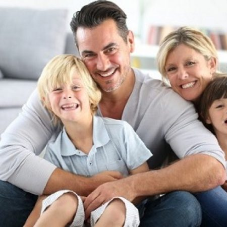 Happy-family-sitting-on-floor-1024x1024 Replacing Missing Teeth with High-Quality Dental Implants